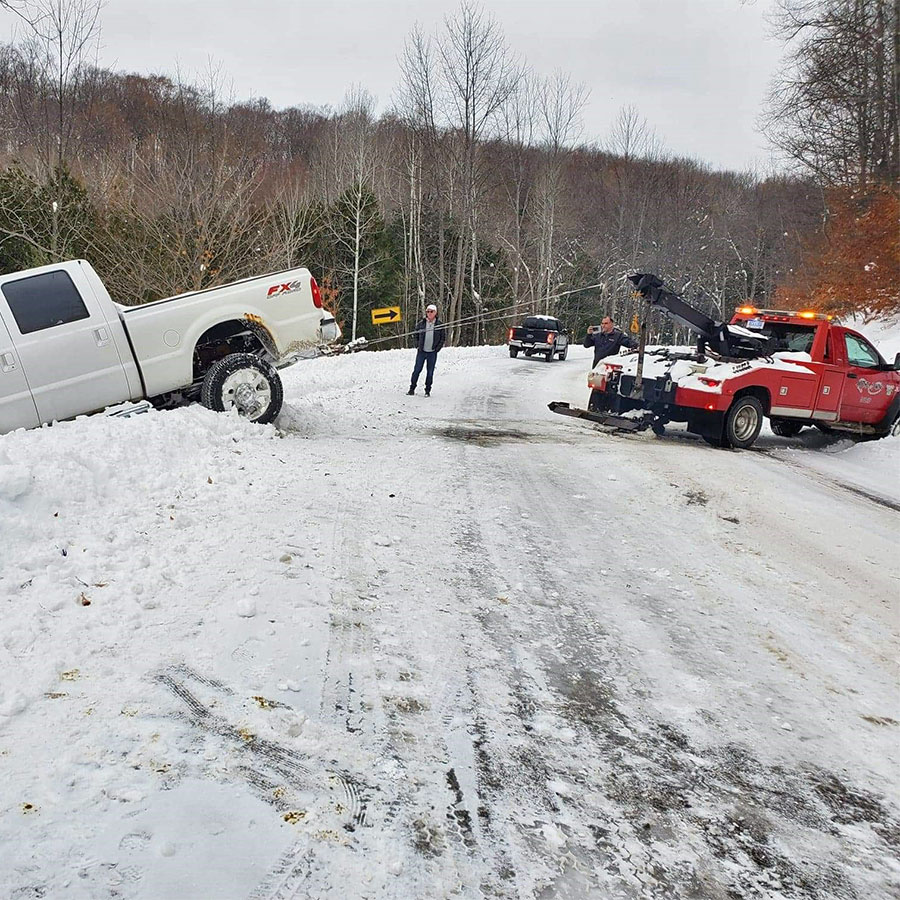 Anytime towing wrecker winching a vehicle out of the ditch